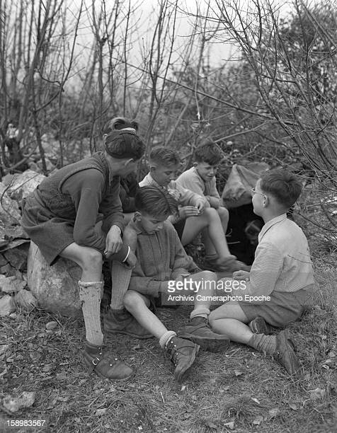 A group of boys sits in the woods surrounding their school Trieste Italy 1946