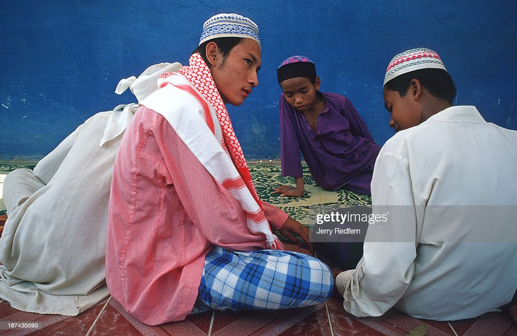 A group of boys wait for the start of Friday noon prayers at the Nour el Essan Mosque in Chong Koh village. The village consists of poor fishing families and a few farmers and traders..