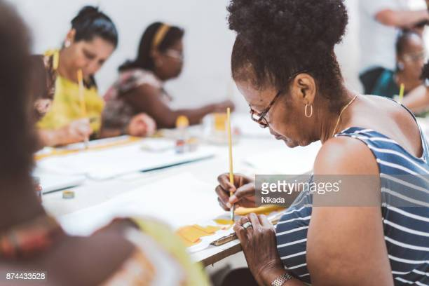 group of brazilian women painting textiles in work room of social project - craft product stock pictures, royalty-free photos & images