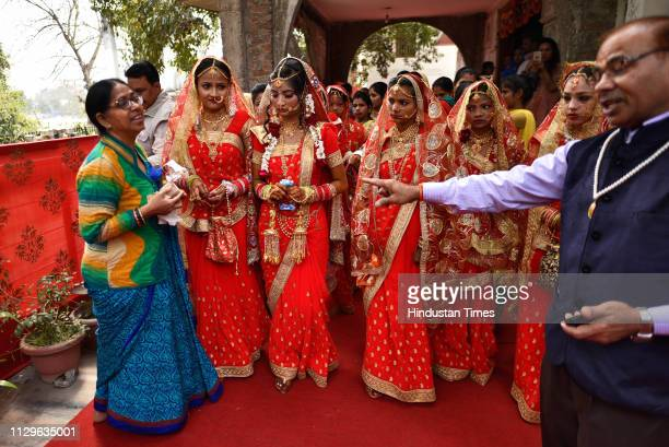 A group of brides walks towards a ritual site during a mass wedding for eight couples at Hanuman Vatika Ramleela Maidan on March 8 2019 in New Delhi...