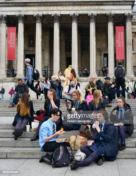 Group of British high school students on a field trip eat their lunches on the steps of the National Gallery in London, England.