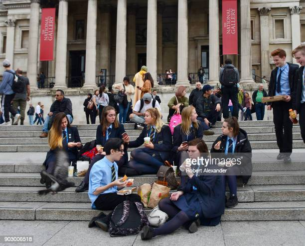 A group of British high school students on a field trip eat their lunches on the steps of the National Gallery in London England