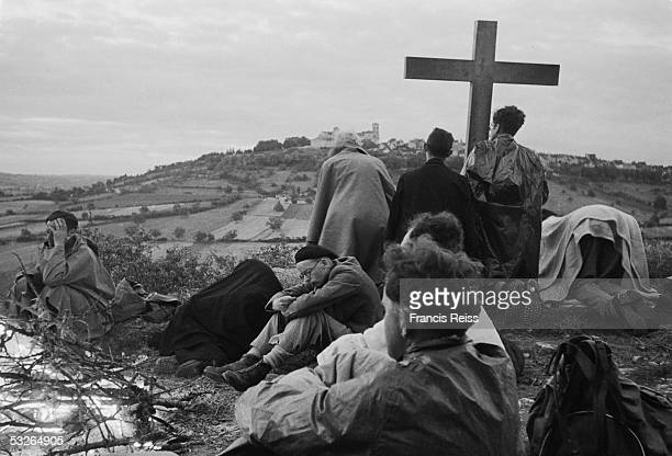 A group of British pilgrims walking through France set up their cross for prayers at dusk in sight of their destination the Benedictine abbey at...