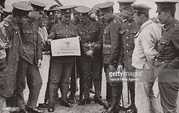 A group of British soldiers read in a copy of the Evening News of the death of British general Horatio Herbert Kitchener 1st Earl Kitchener England...