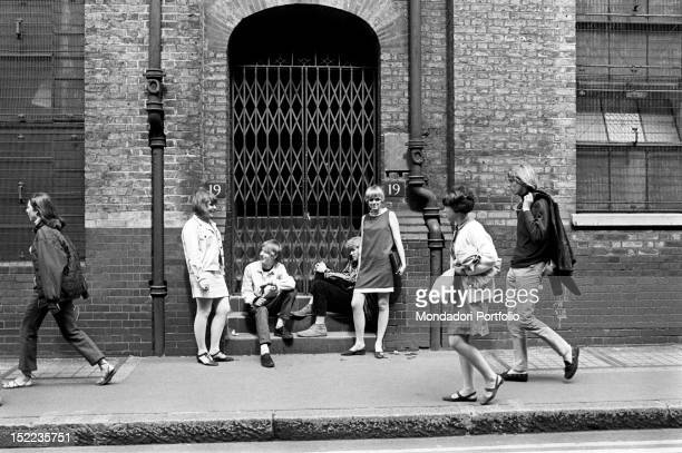 Group of British young people meeting in the street The girls wear a miniskirt and a fashionable minidress London 1960s