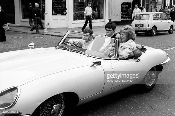 Group of British young people travelling in the streets of the city on an EType convertible Jaguar car London 1960s