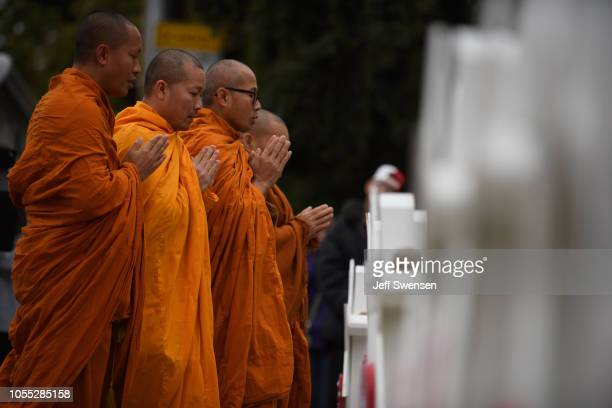 A group of Buddhist monks pray together in front of at a memorial for victims of the mass shooting that killed 11 people and wounded 6 at the Tree Of...
