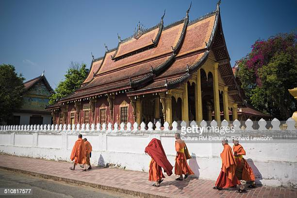 group of buddhist monks walking next to wat sop temple, sisavangvong road, luang prabang, laos, southeast asia - laotian culture stock pictures, royalty-free photos & images