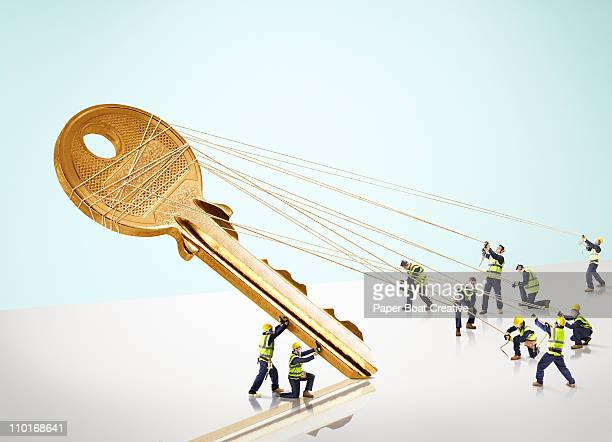 Group of builders carrying a giant gold key