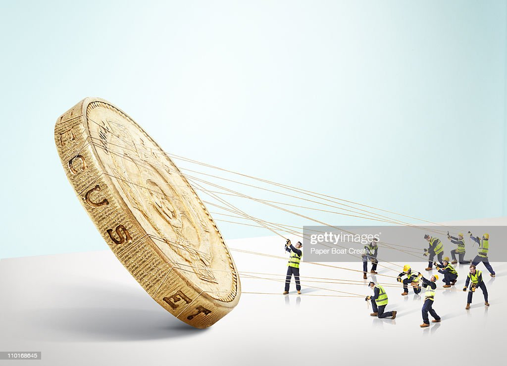 Group of builders carrying a large gold Pound coin : Foto de stock