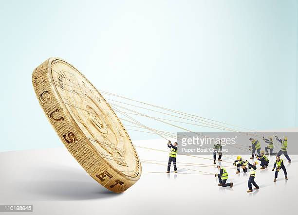 group of builders carrying a large gold pound coin - small stock pictures, royalty-free photos & images