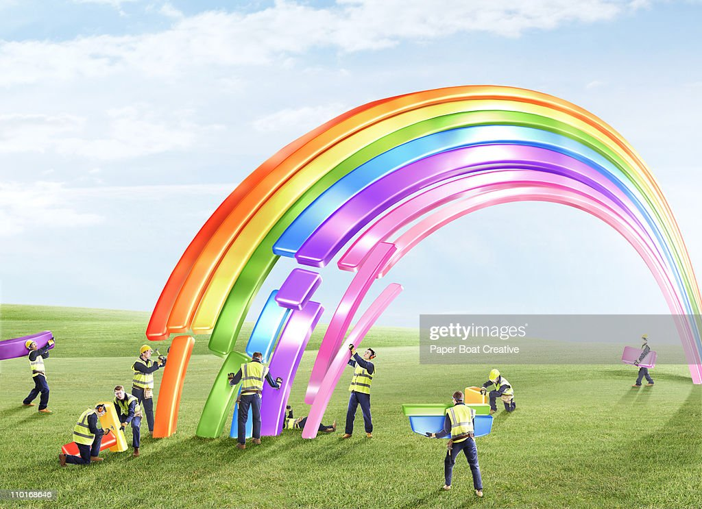 Group of builders fixing a giant plastic rainbow : Foto de stock