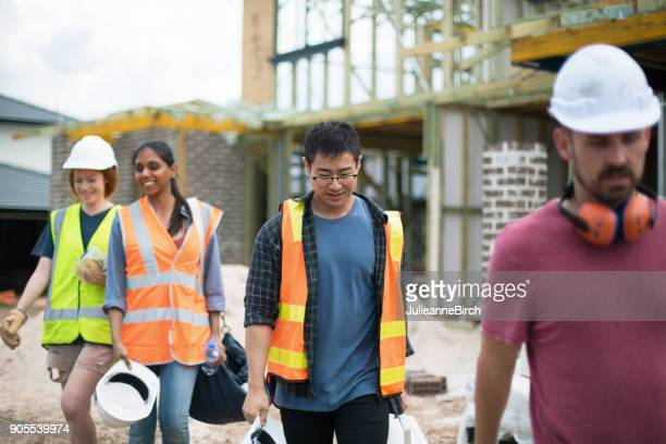 group of builders on construction site leave for home - after work stock photos and pictures