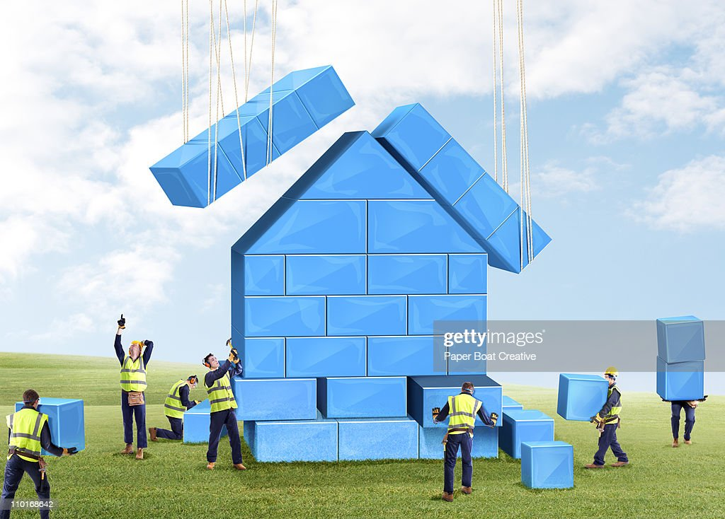 Group of builders putting together a toy house : Stockfoto