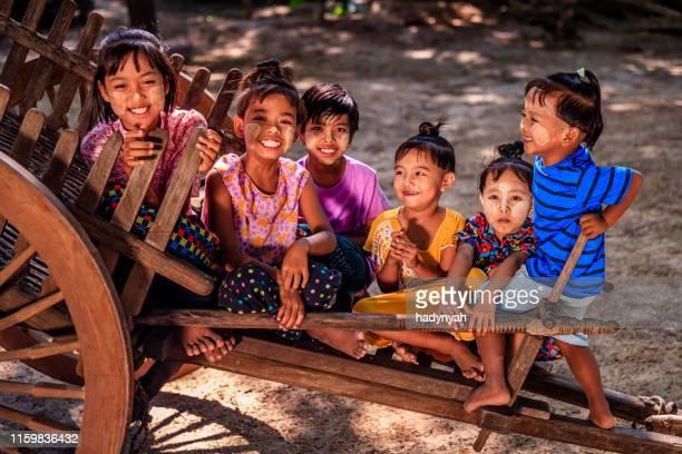 grupo de niños birmanos sentados en el carro de vacas en el pueblo cerca de bagan, myanmar - myanmar fotografías e imágenes de stock