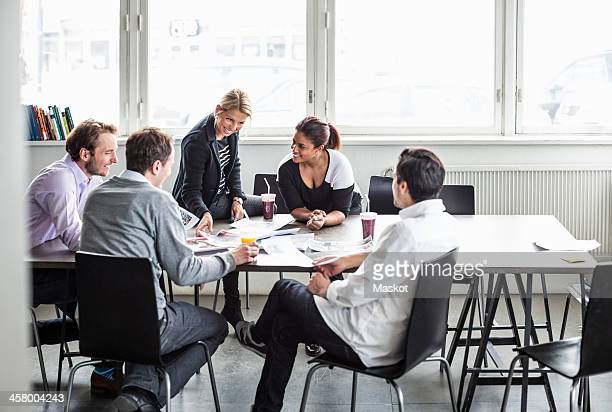 Group of business colleagues discussing at desk in office