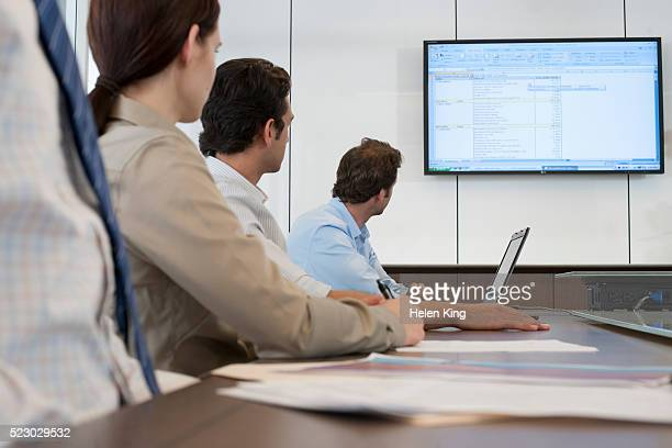 Group of business colleagues looking at presentation in conference room
