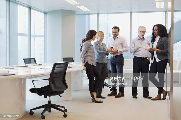 Group of business colleagues standing together talking in open office