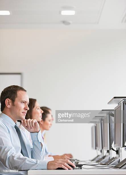 Group of business executives in row working on computer at office