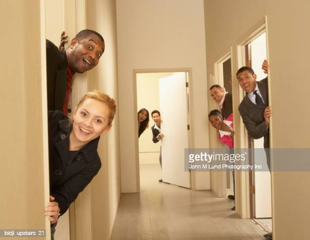 Group of business executives peeking out from the doors