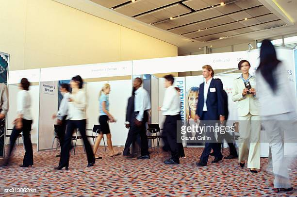 group of business executives walking at an exhibition - tradeshow stock pictures, royalty-free photos & images