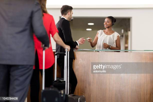 group of business men talking to receptionist - hotel key stock photos and pictures