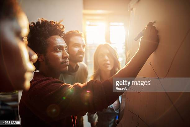 group of business people analyzing a graph in the office. - solution stock pictures, royalty-free photos & images