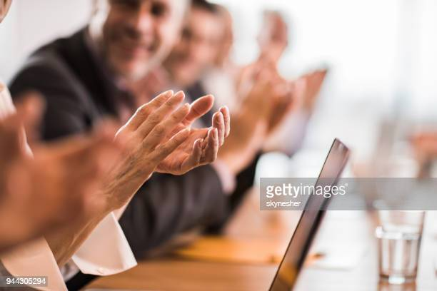 Group of business people applauding on a meeting in the office.