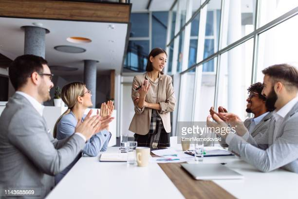 group of business people applauding team leader after presentation - participant stock pictures, royalty-free photos & images