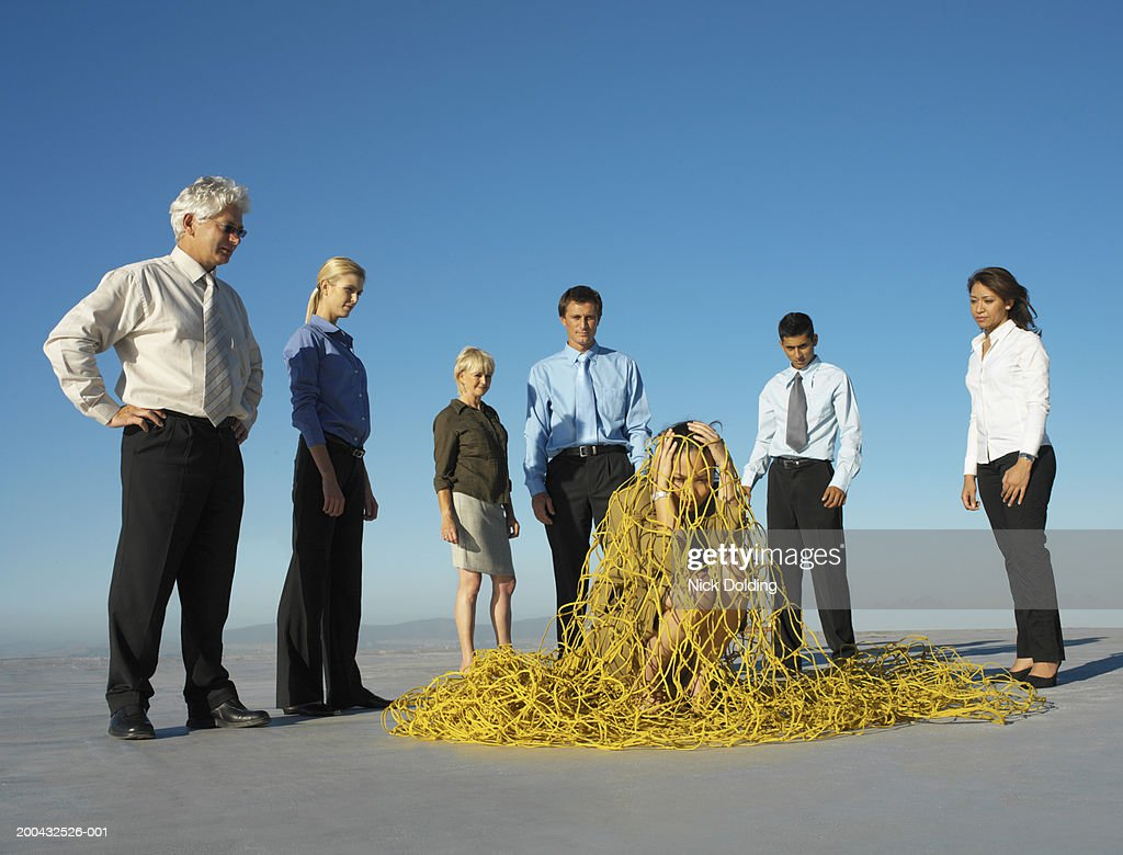 Group of business people catching business woman in net on roof : Stock Photo