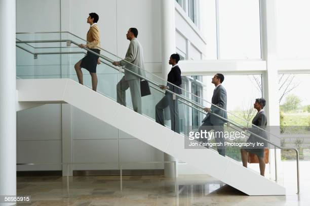 group of business people climbing stairs - following stock pictures, royalty-free photos & images