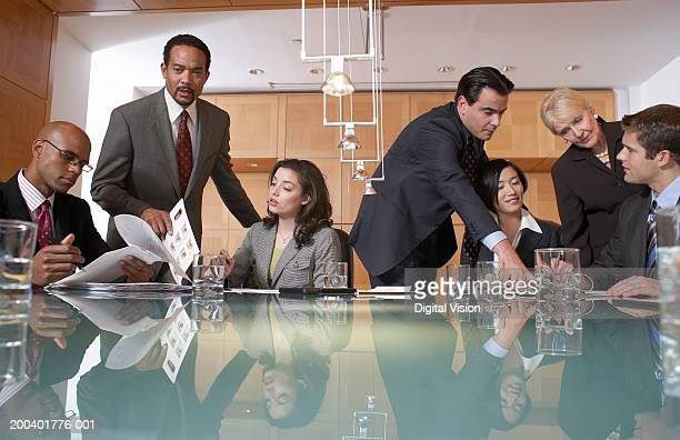 Group of business people conversing in conference room, view across table