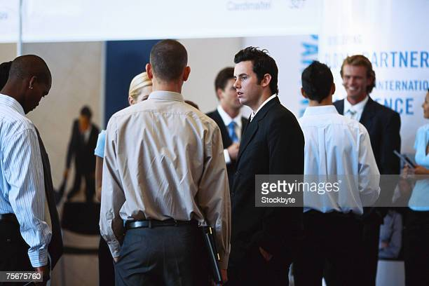 group of business people discussing at exhibition - tradeshow stock pictures, royalty-free photos & images