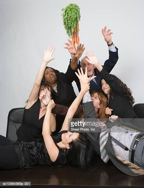 Group of business people fighting for bunch of carrot