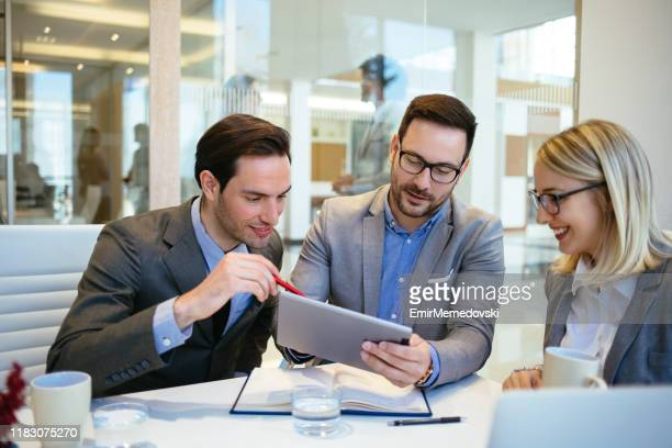 gruppe von geschäftsleuten, die ein meeting mit einem digitalen tablet abführen - organised group stock-fotos und bilder