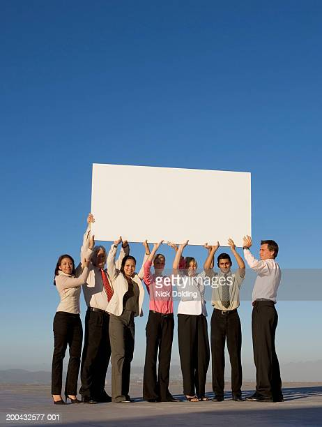 Group of business people holding a blank board on roof