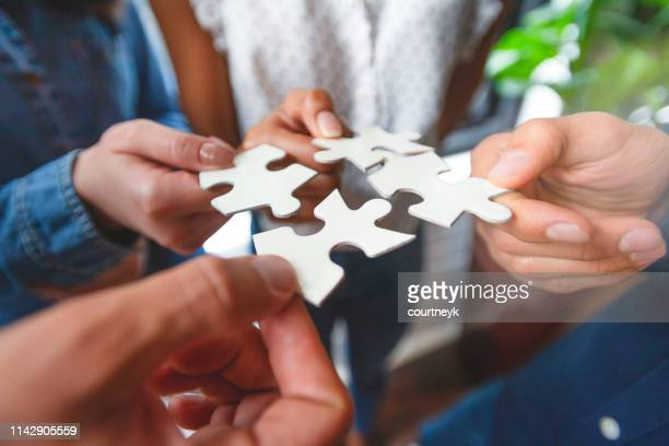 group of business people holding a jigsaw puzzle pieces. - orthodoxy stock pictures, royalty-free photos & images