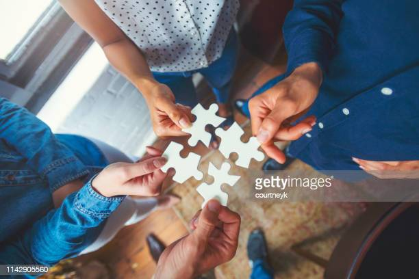 group of business people holding a jigsaw puzzle pieces. - conformity stock pictures, royalty-free photos & images