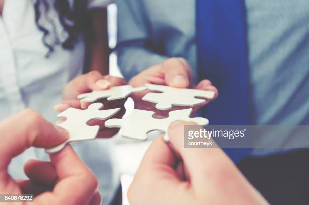 group of business people holding a jigsaw puzzle pieces. - solutions stock pictures, royalty-free photos & images