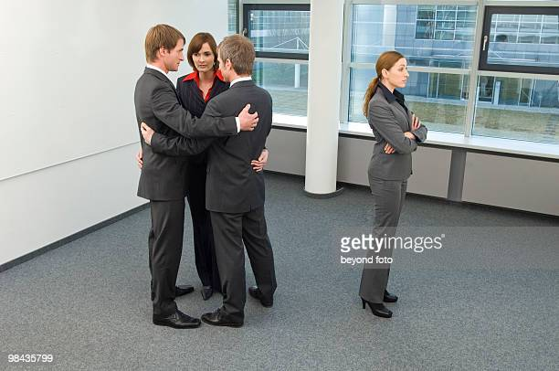 group of business people huddling together excluding female colleague