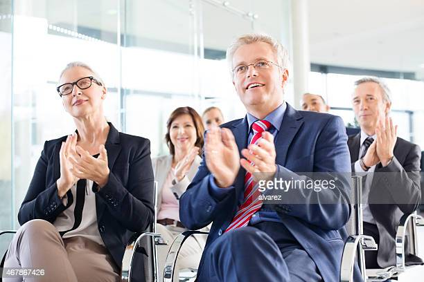 Group of business people in a seminar applauding
