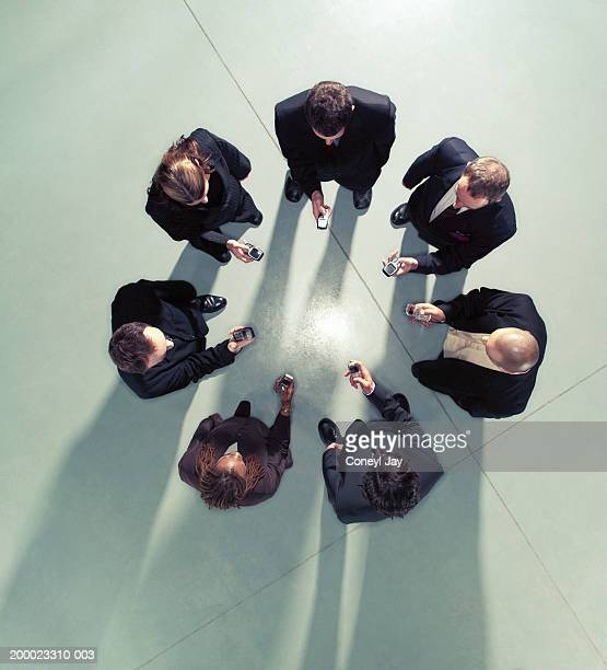 Group of business people in circle using mobile phones, overhead view