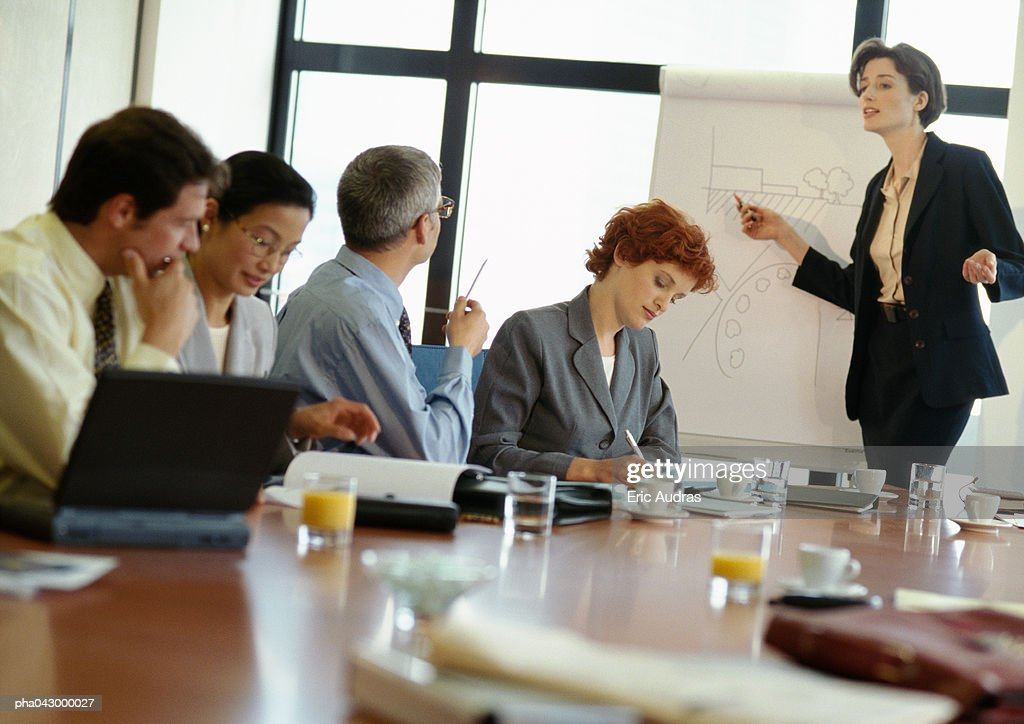 Group of business people in conference room, businesswoman pointing at presentation board : Stockfoto