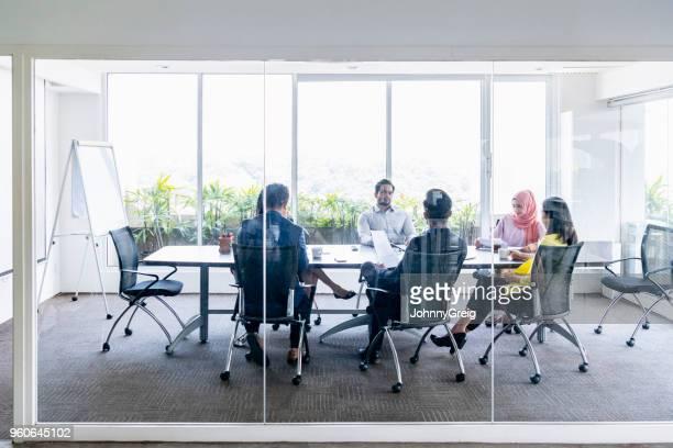 groep van mensen uit het bedrijfsleven in office vergadering achter glas - conferentietafel stockfoto's en -beelden