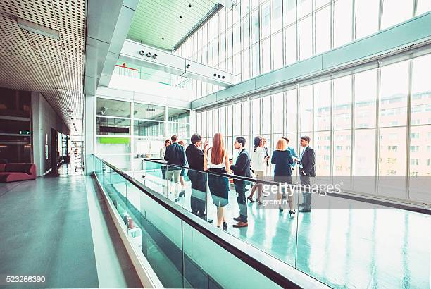 group of business people in the office building lobby - wide angle stock pictures, royalty-free photos & images