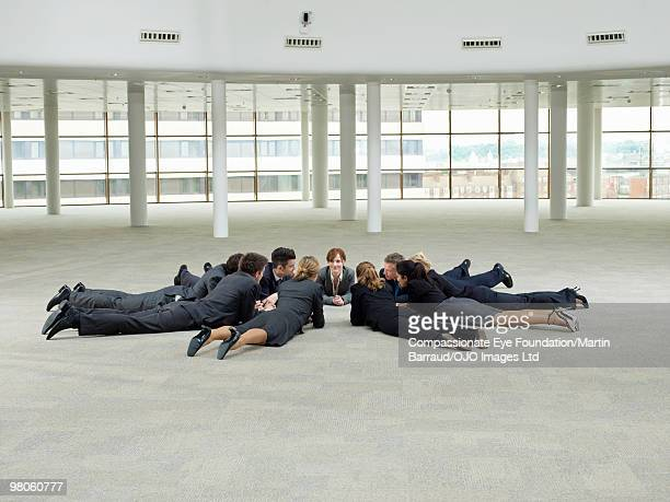 group of business people laying in a circle