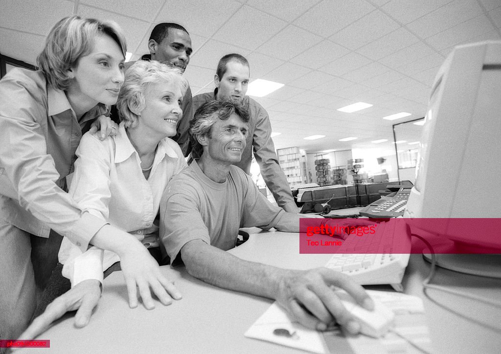 Group of business people looking at computer, B&W : Stockfoto