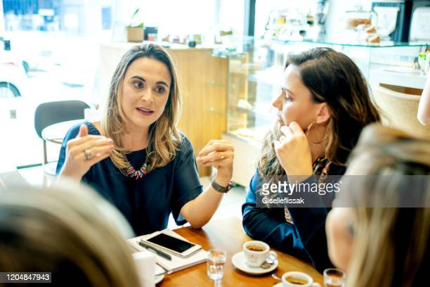 group of business people meeting in a coffee shop - small group of people stock pictures, royalty-free photos & images