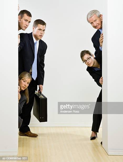 Group of business people peeking around corner