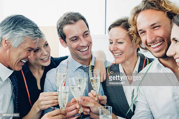 Group of business people raising a toast with champagne at office